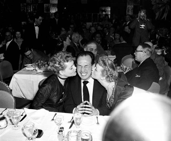 Jose Ferrer is kissed by Judy Holliday, left, and Celeste Holm at a party at a New York night club following presentation of the 1950 annual Academy Awards on March 29, 1951. Ferrer won for best performance by an actor