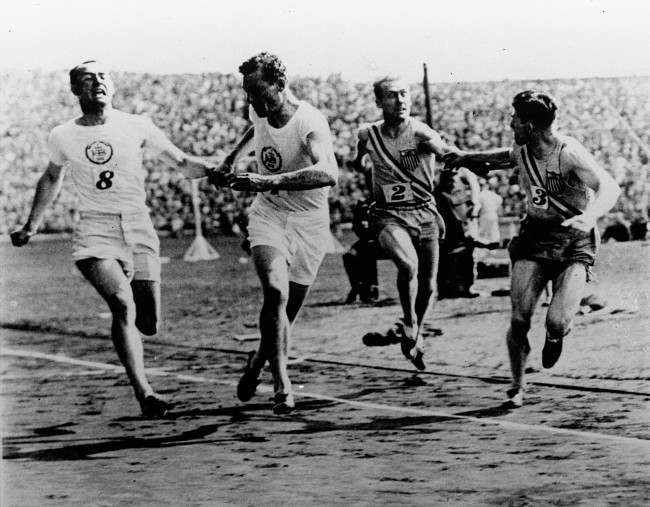 John Rinkel of Britain passes the baton to teammate Roger Leigh-Wood while American Taylor passes the baton to Raymond Barbuti during a meet between the U.S. and British Olympic relay teams at Stamford Bridge, England August 20, 1928. The U.S. team won the relay, setting the one-mile mark of 3 minutes, 13 2/5 seconds.