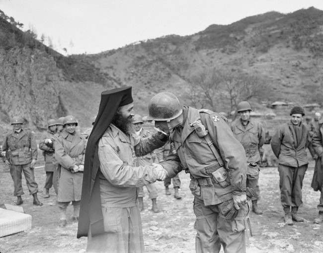 Lt. General Matthew B. Ridgway, U.S. 8th army commander, kisses the cross held by Chaplain Theofanis Tratolos, Greek Orthodox priest attached to the Greek battalion fighting in Korea, during the latter's celebration of independence Day on the central front in Korea on March 31, 1951. Ridgway later reviewed the unit which has won an outstanding combat reputation while fighting with U.N. forces against the Reds.
