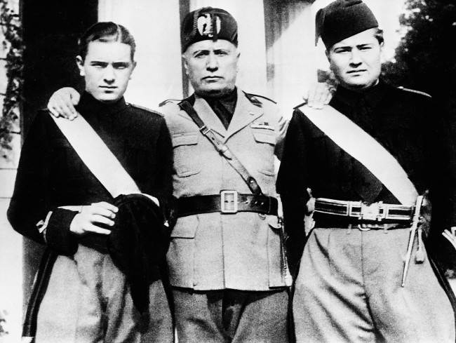 Italy's Premier Benito Mussolini, center, stands with an arm over the shoulders of his two sons, Bruno, left, and Vittorio during the young Fascists' Festival in Rome, Italy, March 14, 1935