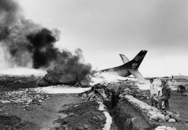 An American C-123 cargo plane burns after being hit by communist mortars while taxiing on marine post at Khe Sanh, South Vietnam on March 1, 1968.