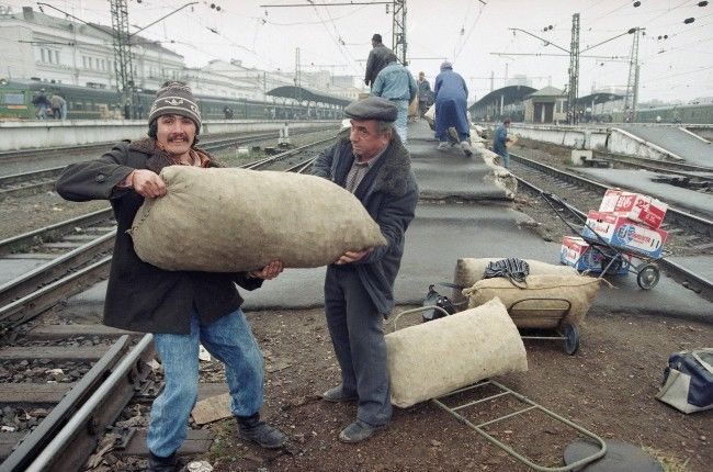Two Ukrainian farmers from Crimea peninsula region unload sacks with walnuts at the Kurski railway station in Moscow, Oct. 13, 1993. Growers from outside Russia, primarily the Caucasians from Azerbaijan, Georgia and Armenia have faced increasing difficulty selling their goods in Moscow with the state of emergency. Drivers and passengers coming into Moscow must produce local residency papers or face deportation.