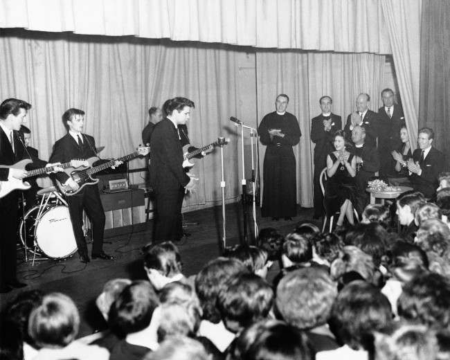 Princess Margaret and her husband, Lord Snowdon, applaud from their table at right, as pop singer Cliff Richard sings at a youth club in London's Hackney district, March 22, 1962. The princess was the center of a stamping, whistling group of teenagers.