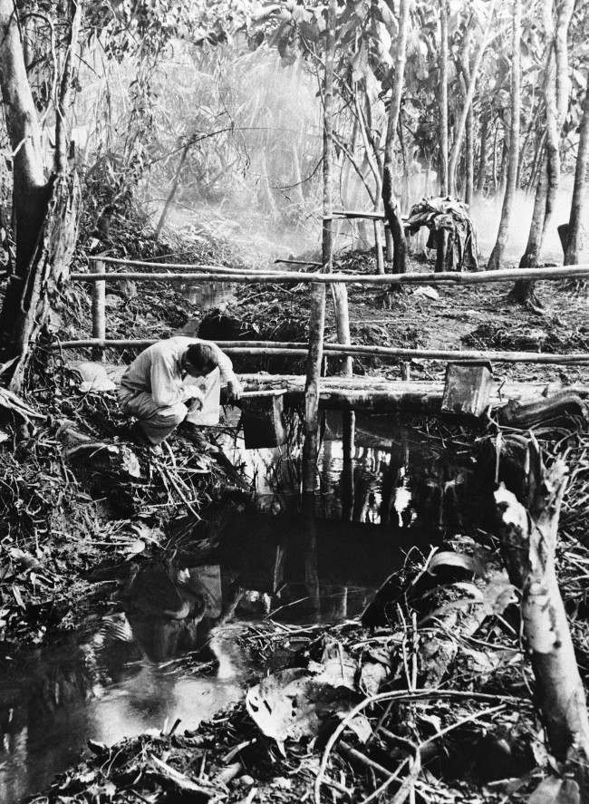 A U.S. soldier checks the oil supply in a drip can suspended from a foot bridge by Malaria control experts near a U.S. Army camp on South West Pacific Island of New Guinea, on August 26, 1944. Oil dripping from the can coats the surface of the sluggish stream and kills the larvae of Malaria-bearing mosquitoes.
