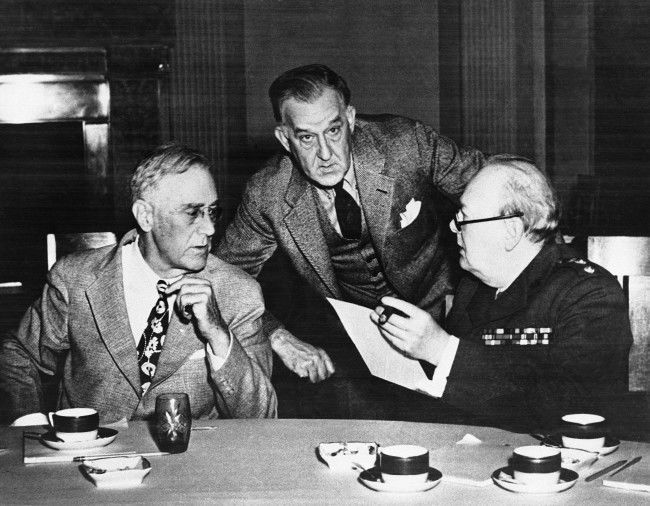 US President Franklin D. Roosevelt, left, confers with British Prime Minister Winston Churchill, right, during luncheon at the Livadia Palace in Livadiya on Feb. 18, 1945, where the Crimea Conference was held. President Roosevelt's Secretary, Stephen Early, stands in back of the two Allied leaders.