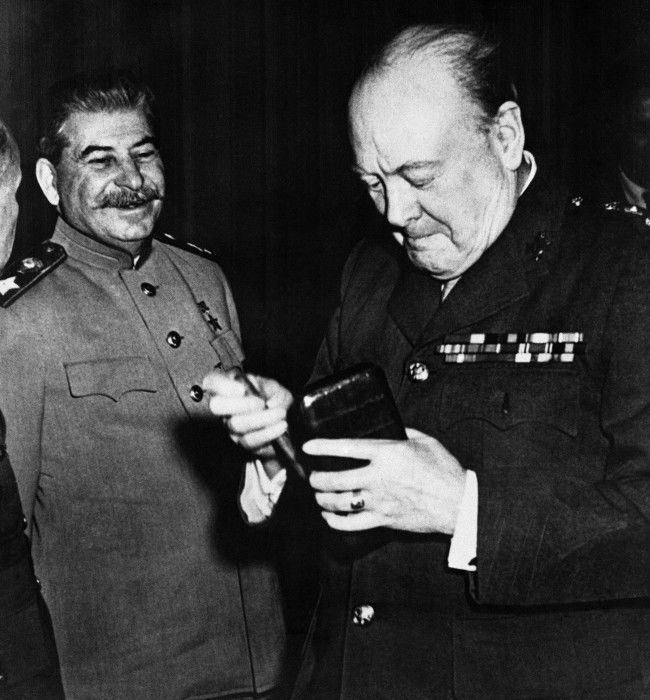 Britain's Prime Minister Winston Churchill, who takes from his case a fresh cigar as Soviet Marshal Josef V Stalin smiles approvingly between sessions of the Crimea Conference, held at Yalta, Ukraine, on Feb. 17, 1945.