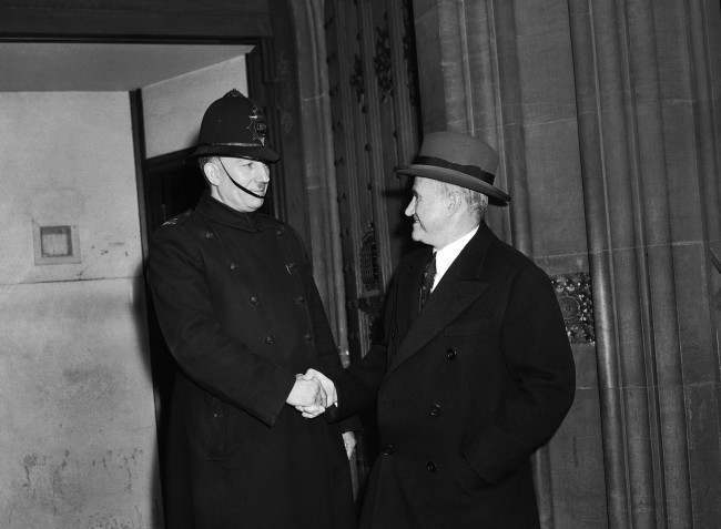 Among those who attended the opening of the 3-day debate on the Crimea Conference at the House of Commons, London, on Feb. 27, 1945, to hear Winston Churchill's opening speech, was Sam Goldwyn, the American film producer, now visiting this country. Sam Goldwyn shakes hands with the constable on duty at the House of Commons.
