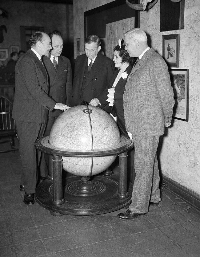 Left to right: Sir George Hubert Wilkins, explorer and writer; Joseph Robinson, secretary of the Explorers' Club; Walter Granger, president of club; Lady Grace Drummond Hay, writer; and Dr. H. J. Spinden, director of the Brooklyn Museum, study the route of the Zeppelin Hindenburg's flight to America on a globe at the Explorers'' Club in New York on May 10, 1936.