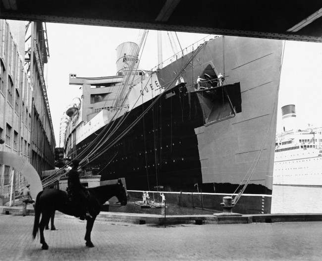 Workmen give the Queen Mary, pride of Great Britain's merchant marine, a paint t of battleship gray, at the Cunard Line in New York Sept. 13, 1939, where the liner was docked. The new coat of paint will serve as a camouflage for the big ship and when she sails for home waters.