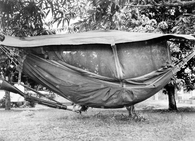 U.S. troops engaged in jungle maneuvers in Panama, August 5, 1942, have two methods of sleeping -- in a canopy-covered hammock (above) suspended from trees or on the ground (below) covered by cloth for protection against insects. Note rifle suspended from hammock.