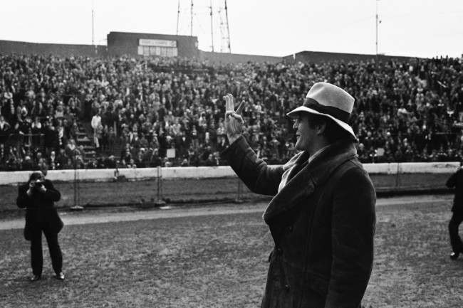 Manager of Crystal Palace Football Club Malcolm Allison wearing a hat, indicates his team's three goals to the fans at Stamford Bridge, London on Feb 15, 1976. Palace beat Chelsea 3-2 in the FA Cup match. (AP Photo/Peter Kemp) Ref #: PA.9639056  Date: 15/02/1976