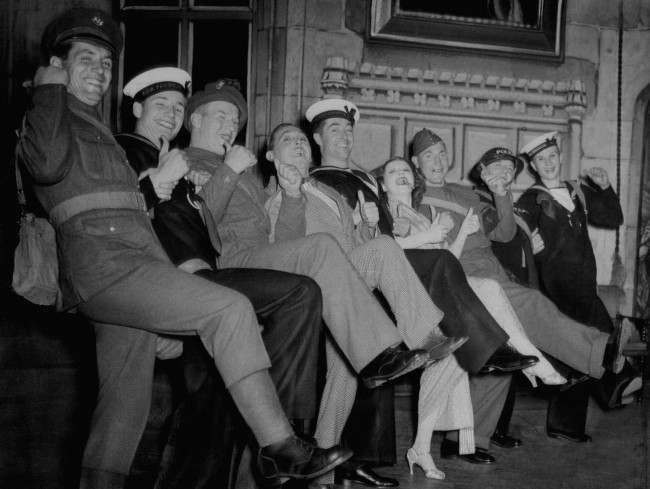 "Soldiers and sailors joined principals of ""Me and My Girl"", musical comedy, in the Lambeth Walk on the stage of the Victoria Palace in London after a performance, Oct. 6, 1939. (AP Photo) Date: 06/10/1939"