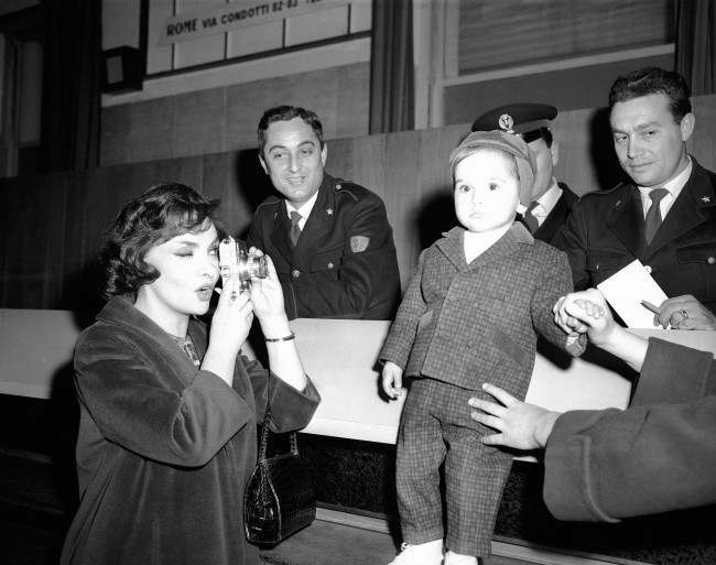 Like any other doting mother, actress Gina Lollobrigida takes pictures of her 19-month-old son, Milko Jr., at Rome's Ciampino Airport, March 13, 1959 as they awaited arrival of Gina's husband, Dr. Milko Skofic. Airport police were interested spectators.