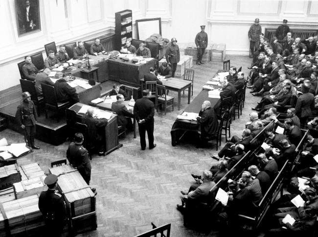 In Kaunas, the capital of Lithuania, the big Antinational socialist trial is getting on in the Ministry of justice on March 15, 1935. In the left corner one sees several boxes filled with rifles, that were found at the arrested 126 people. Centre one remarks the military court, on the right side all banches are filled with the accused arrestants.4