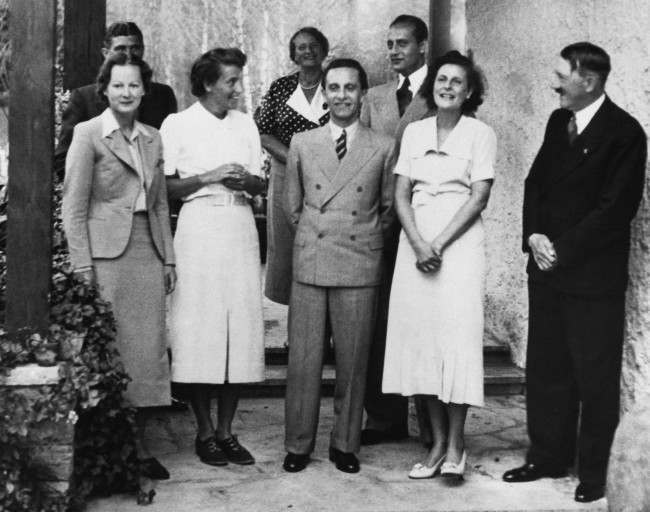 German filmmaker Leni Riefenstahl, second from right, stands beside Chancellor Adolf Hitler, right, during Hitler's call on the film director at Riefenstahl's Berlin mansion. From left to right: Ilse Riefenstahl, her sister; behind her, Capt. Fritz Wiedemann, Hitler's adjutant; Mrs. Ebersberg (no other information available); Bertha Riefenstahl, Leni's mother; propaganda minister Joseph Goebbels; Heinz Riefenstahl, Leni's brother; Riefenstahl, and Hitler. Date: 03/10/1938