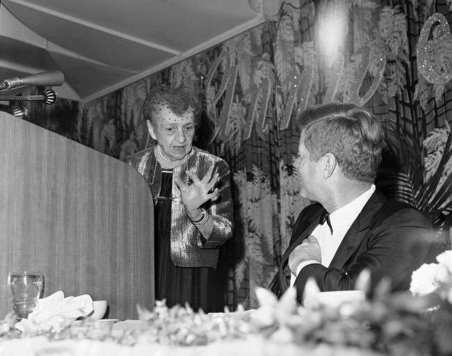 """Former Secretary of Labor Frances Perkins evokes a smile from President John Kennedy during her speech at a dinner in Washington March 4, 1963 to celebrate the 50th anniversary of the Labor Department. Miss Perkins indicates with her fingers the size of """"New England cockroaches"""" with which she was familiar in her early days in New England. She said she found a much larger variety in her desk in the old when she became Labor Secretary in the Franklin D. Roosevelt cabinet in 1933."""