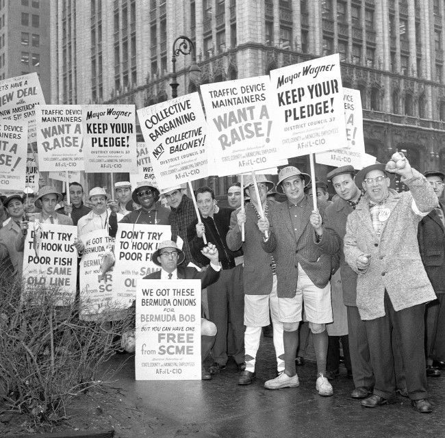 "City employes protesting threats of reductions in the size of promised pay increases demonstrate at New York's City Hall Park March 31, 1959. They numbered about 2,000 police estimated. Some wore Bermuda shorts and carried fishing poles in reference to Bermuda vacation which Mayor Robert Wagner concluded the night before. Mayor blamed state government for ""short-changing"" the city and said municipal employes who left jobs to demonstrate would do so at their own expense."