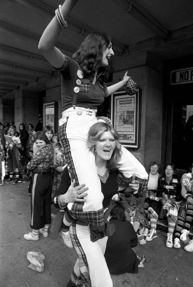 High spirits from two fans of the Bay City Rollers, as they wait with other fans for the doors to open at the Odeon, Hammersmith, for the first of two concerts by the group. PA/PA Archive/Press Association Images.