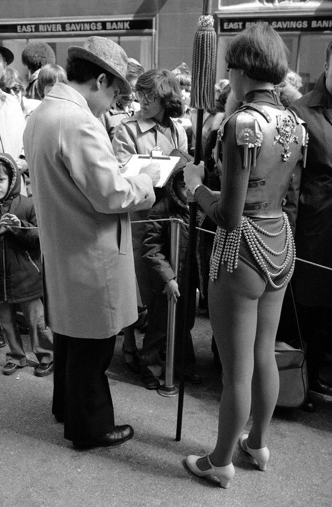 Rockette Cindy Peiffer, dressed in armor suit, right, waits outside New York City's radio city music hall on April 2, 1978 as a man signs a petition to extend the life of the famous showplace. Rockettes and Radio City Music Hall employees gathered the signatures of many people who were on line to see the Easter show. The music hall is scheduled to close on April 12.