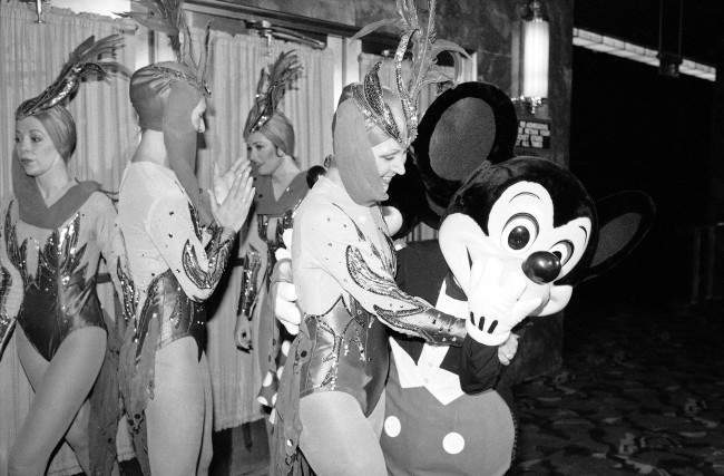 A Mickey Mouse character and one of the Rockettes hug each other at Radio City Music Hall in New York on Feb. 1, 1985. Walt Disney Productions has changed its mind and will allow the high-kicking Rockettes to appear in the summer show at Radio City Music Hall, the hall announced on Friday.
