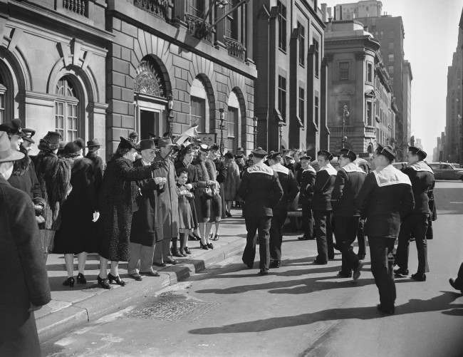 Following attendance at pontifical mass in St. Patrick's Cathedral in New York on Feb. 28, 1943, one hundred sailors from the French battleship Richelieu were guests at the Cathedral Canteen, 17 East 51st Street. On their way across the street for their quotas of coffee, tea or milk and pastry, the French seamen were cheered by this elderly woman, shown waving a tri-color flag and crying 'Vive La France.'
