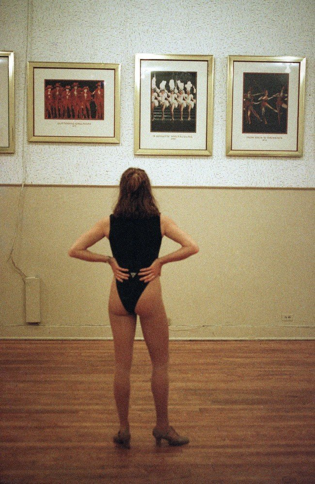 A Rockette hopeful looks at pictures of the dance troope while waiting her turn to strut her stuff before a panel of judges during open auditions at New York's Radio City Music Hall on March 11, 1993. An annual affair, scores of women try to aspire to be part of one of the most famous entertainment institutions in the world.