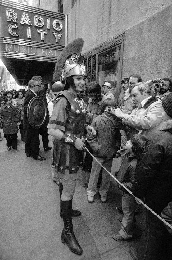Costumed Rosemary Novellino, one of the famed Radio City Music Hall Rockettes, joins other Music Hall employees in collecting signatures on petitions to keep the historic hall open in New York on April 2, 1978. The music hall staff, some pressed in costumes, collected the signatures from crowds in line for Sunday, April 2, performance. The music hall is scheduled to close on April 12.