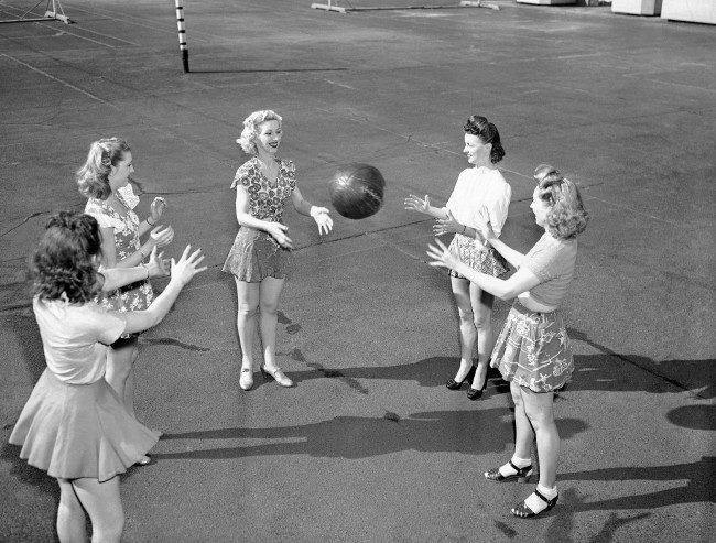On a warm spring day, some of the Rockettes get exercise with a medicine ball on the Music Hall roof in New York on March 26, 1946. The roof is a summertime center of leisure-time activities for the theater's employees. It has a handball court, paddle tennis ture for sunbathing and relaxation. Parties and dances are given on the roof.