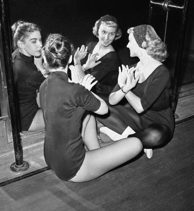 In front of a mirror in the film theater's rehearsal hall, Mary Ann Strilka (right) and Jean Mullenix practice hand movements on Oct. 15, 1958. They are two of the Rockette dancers in New York.
