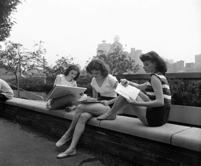 Enjoying the benefit of the sun, dressed in rehearsal costumes, on the play roof of Manhattan's Radio City Music Hall, these three Rockettes sketch the skyline between shows in New York on June 13, 1951. The girls study art at the American Art School in Manhattan in their free time.
