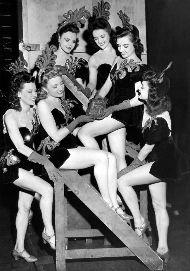 "Radio City Music Hall Rockettes admire plaque, made from wood and metal fragments of a Japanese plane downed by Navy fliers in the South Pacific, in New York on June 20, 1944. Inscription reads: ""The Fighter Direction Center, South Pacific, have selected as our sponsor and ideal, the Radio City Rockettes, New York."" Left to right: (top row) Jean MacLeod, Newark, N.Y.; Edna Mae Powers, New Rochelle, N.Y.; Suzanne Graves, Kansas City, Mo.; (bottom row) Mollie Pearson, Brooklyn, N.Y.; Anne Collins, Elkton; and Marian Block, Columbus, Ohio."