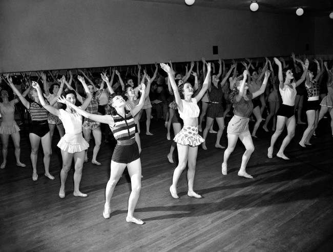 Back in the line, Radio City Music Hall Rockettes, Corliss Fyfe, Eleanor Dunne, Ginnie Volmer and Pat White, get down to being dancers again in New York on June 13, 1951. When free from rehearsals, or on stage, the girls study and practice their art of sketching and painting.