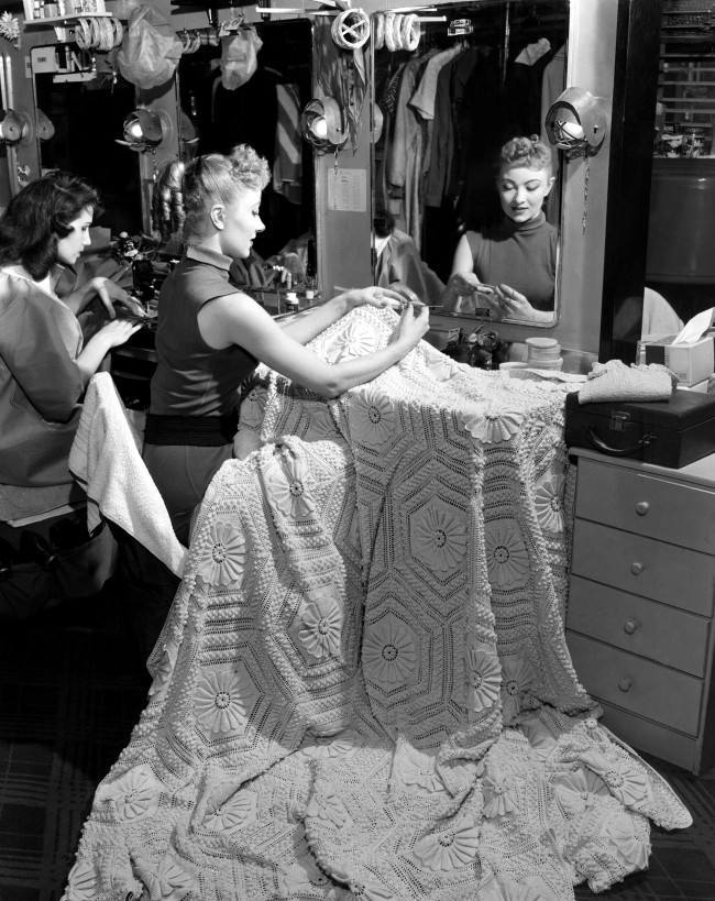 Jane Freund crochets a bedspread while a fellow dancer sews at a machine in one of dressing rooms backstage of New York's Radio City Music Hall between the two-hour waits for their shows as the Rockettes, on Feb. 13, 1958.