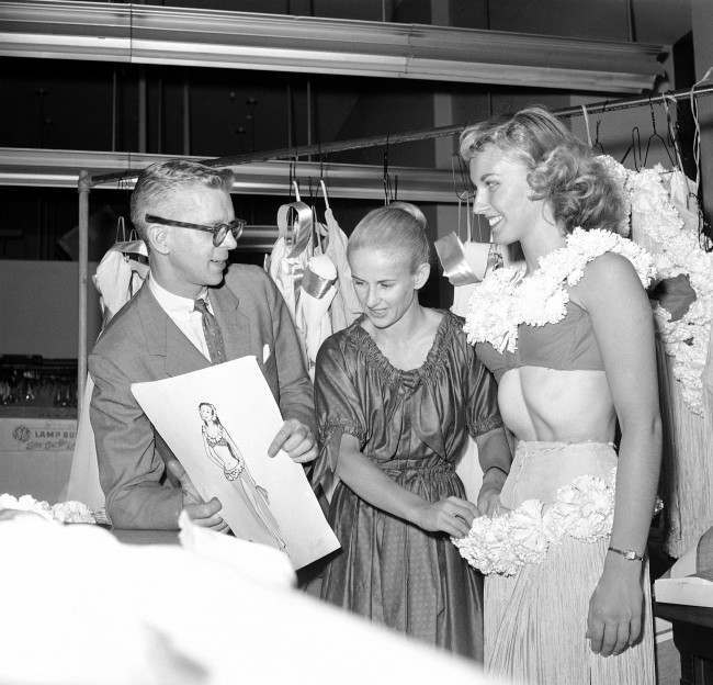 A hula costume is fitted on dancer Mary Ann Strilka by Leanne Mitchell in New York on Oct. 15, 1958 while Frank Spencer holds the sketch from which the costume was made. Miss Mitchell is director of the costume department of the Rockettes, and Spencer is the costume designer. Mary Ann is a member of the famed New York dance troupe.