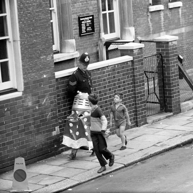 Oblivious of the drama that was going on, a small bow hiding his identity under a Dalek suit, was among the very few spectators as John Edward Witney was ushered out of the West London Magistrate's Court. The boys just went on playing their games. Date: 31/08/1966