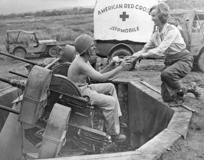Red Cross worker Roxane Pollack (right), of Philadelphia, Pa., hands coffee and doughnuts to Pfc. Marvin Clover, of Clayton, Ala., as he stands guard at his gun position on the fringe of a Dutch New Guinea air base on Oct. 23, 1944. Mobile canteen of the Red Cross is mode of transportation of the food.