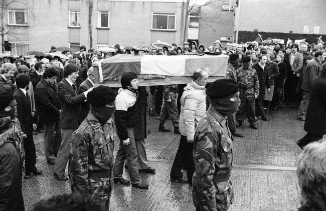 John Sands, (extreme left), puts his hands on his brother Bobby's coffin, as it is escorted by masked IRA men, from his parent's house to a church, in the Twinbrooks area of Belfast, Northern Ireland on May 6, 1981. The coffin will lie in the church overnight, until Thursday's funeral ceremonies at Belfast's Milltown cemetery. (AP Photo/Peter Kemp)