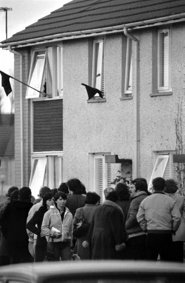 Black flags fly from the windows, as people queue outside the home of Bobby Sands' parents in the Twinbrooks area of Belfast, Northern Ireland on May 6, 1981, to view Sands' body. IRA hunger striker Sands, died in Northern Ireland''s Maze Prison on Tuesday, after 66 days on hunger strike.