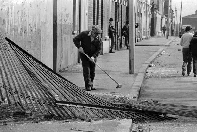 An old man sweeps broken glass outside his home, as a British army patrols a street in the Catholic Falls Road area of Belfast, Northern Ireland on May 6, 1981. After almost 36 hours of sporadic rioting, Belfast was quiet on Wednesday, following the death of IRA hunger striker Bobby Sands.