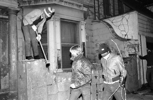 A hooded youngster knocks down a wall with a sledge hammer, to gather bricks for throwing at security forces, as another gathers barbed wire for a barricade in Belfast's Falls Road, Northern Ireland on May 5, 1981. Rioters took to the streets, after hearing of the death of IRA hunger striker Bobby Sands, in the Maze Prison. (AP Photo/David Caulkin)