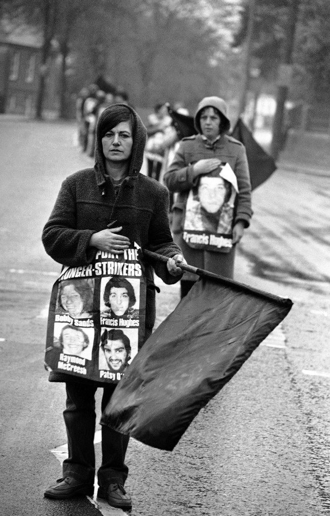 Protestors supporting the H-block protest, wave black flags of mourning for hunger striker Bobby Sands, as they stand in the center of Belfast's Falls Road on May 5, 1981. The protestors were mourning the death of Sands, who died early Tuesday, at the start of his 66th day of hunger strike in Northern Ireland's Maze Prison. (AP Photo/David Caulkin) Ref #: PA.10427033  Date: 05/05/1981