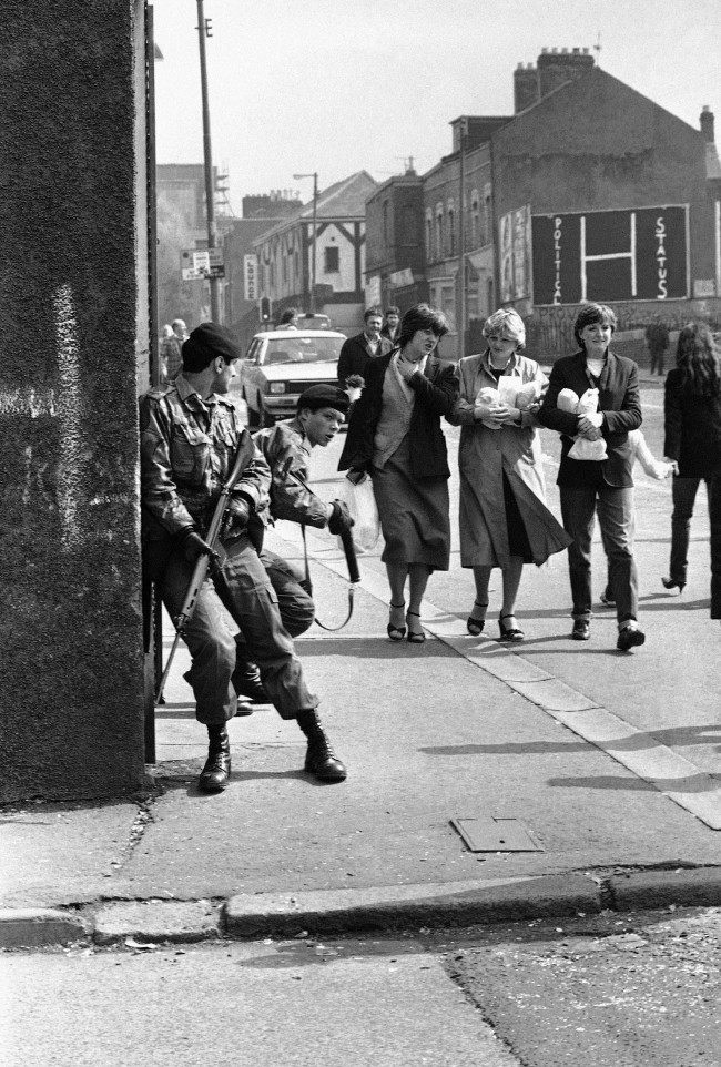 Three young girls stroll along a Belfast street, while two British soldiers of the Royal Fusiliers keep watch for snipers, after a spate of rioting in Belfast, Northern Ireland on May 5, 1981. Although rioters took to the streets in the early hours of the morning, following the death of IRA hunger striker Bobby Sands, much of the city had returned to normal by dawn. (AP Photo/Peter Kemp) Ref #: PA.10427042  Date: 05/05/1981