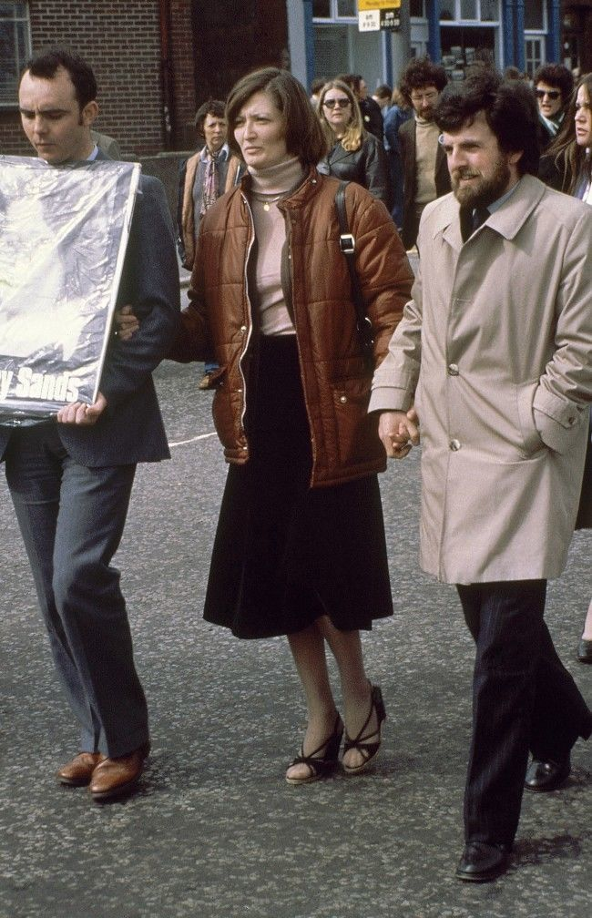 Marcela Sands, sister of Bobby Sands M.P., hunger-striking inmate of the Maze Prison, walks hand in hand with his election agent Owen Crow during a protest rally in Northern Ireland in April 1981. (AP Photo/Peter Kemp) Date: 01/04/1981