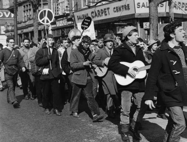 Guitar strumming youths and banner bearers march into London on April 18, 1960 in the 20,000 strong procession of anti a bomb demonstrators protesting against the manufacture of nuclear weapons? The procession is heading for Trafalgar Square London, where huge anti bomb rally is scheduled. (AP Photo) Ref #: PA.10742786 Date: 18/04/1960