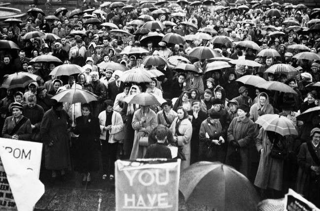 An huge crowd, mostly women sheltered under their umbrellas in Trafalgar square, London on May 12, 1957, at a mass meeting of the national council for the abolition of nuclear weapon tests. The rally was organized as a women's protest march against H-bomb tests from Hyde Park to Trafalgar square. (AP Photo) Ref #: PA.10742792 Date: 12/05/1957