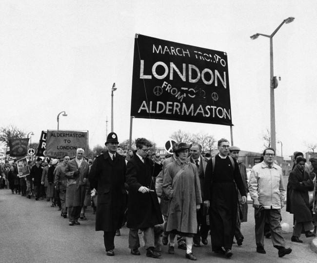 "Demonstrators start out on April 15, 1960 from Aldermaston, England, on 54-mile ""Ban-the-Bomb"" protest march to London. Second from right, front, is canon John Collins of St. Paul''s Cathedral, a member of the campaign for nuclear disarmament, which organized the four-day Easter march for the third successive year. March began with some 9,000 demonstrators from a field near the Aldermaston atomic weapons research establishment. Another 6,000 demonstrators were expected to join the march before it ends with a mass rally in London's Trafalgar Square on April 18. (AP Photo) Ref #: PA.10742810  Date: 15/04/1960"