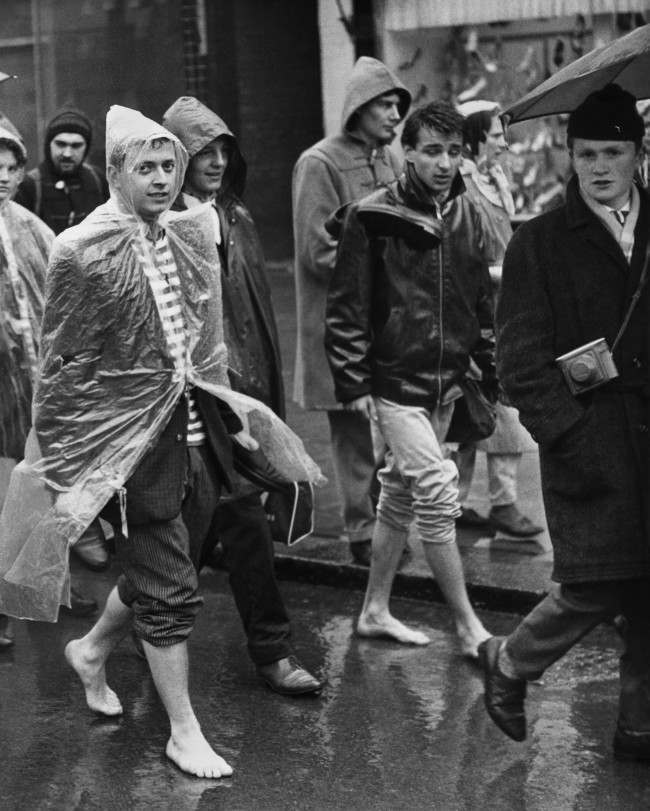 "A couple of barefooted youths with trousers rolled up trudge through Cheswick, west London, in the rain on April 3, 1961, as the Aldermaston column of ""Ban-the-bomb"" marchers set off on the last weary lap of their long trek to Trafalgar Square. Another column of marchers is converging on Trafalgar Square from Wethersfield, Essex, where there is a U.S.A.F. base. They spent the night in East London."