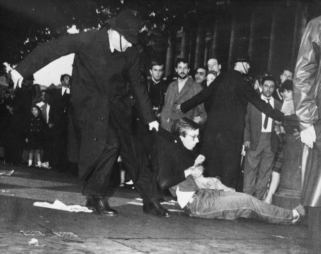 A young man in beatnik-style clothes is dragged along by a policeman