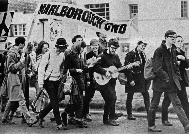 "Teenagers in jeans, sweaters and duffle coats march to the accompaniment of a guitar as the 10,000 ban-the-bomb marchers leave Reading, Berkshire on April 21, 1952, on the second leg of their protest march from Aldermaston to London. They are marching under a banner reading ""Marlborough CND"" (Campaign for Nuclear Disarmament)."