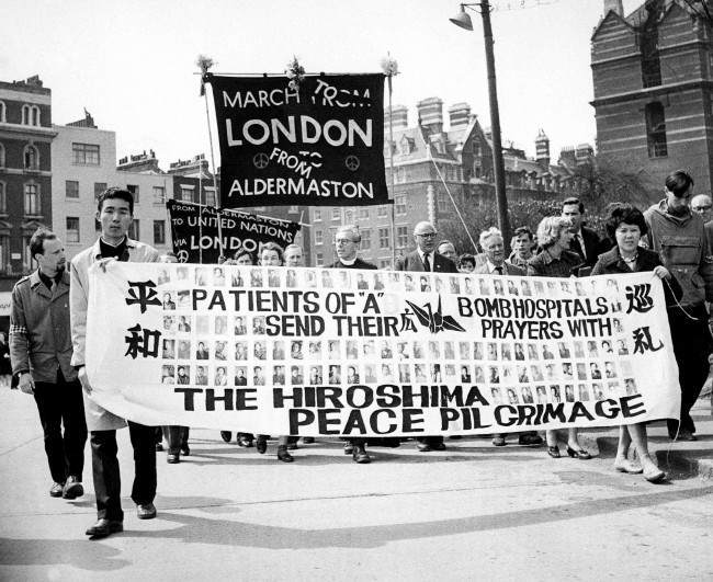 "Two survivors of the Hiroshima atomic bomb, 29-year-old nurse Miyoko Matsubara and law student Hirosama Hanabusa, 18, join the column of British nuclear disarmers as the demonstrators file into London's Hyde Park on April 23, 1962, for the mass rally climaxing their Easter March from Aldermaston, 50 miles from London. The couple, who call themselves ""The Japanese Peace Pilgrims,"" hold a big banner carrying pictures of patients still in hospital suffering with effects from the atomic bomb. Behind the banner is Canon John Collins, chairman of the campaign for nuclear disarmament, and next to him, at right, is trade union leader Frank Cousins."